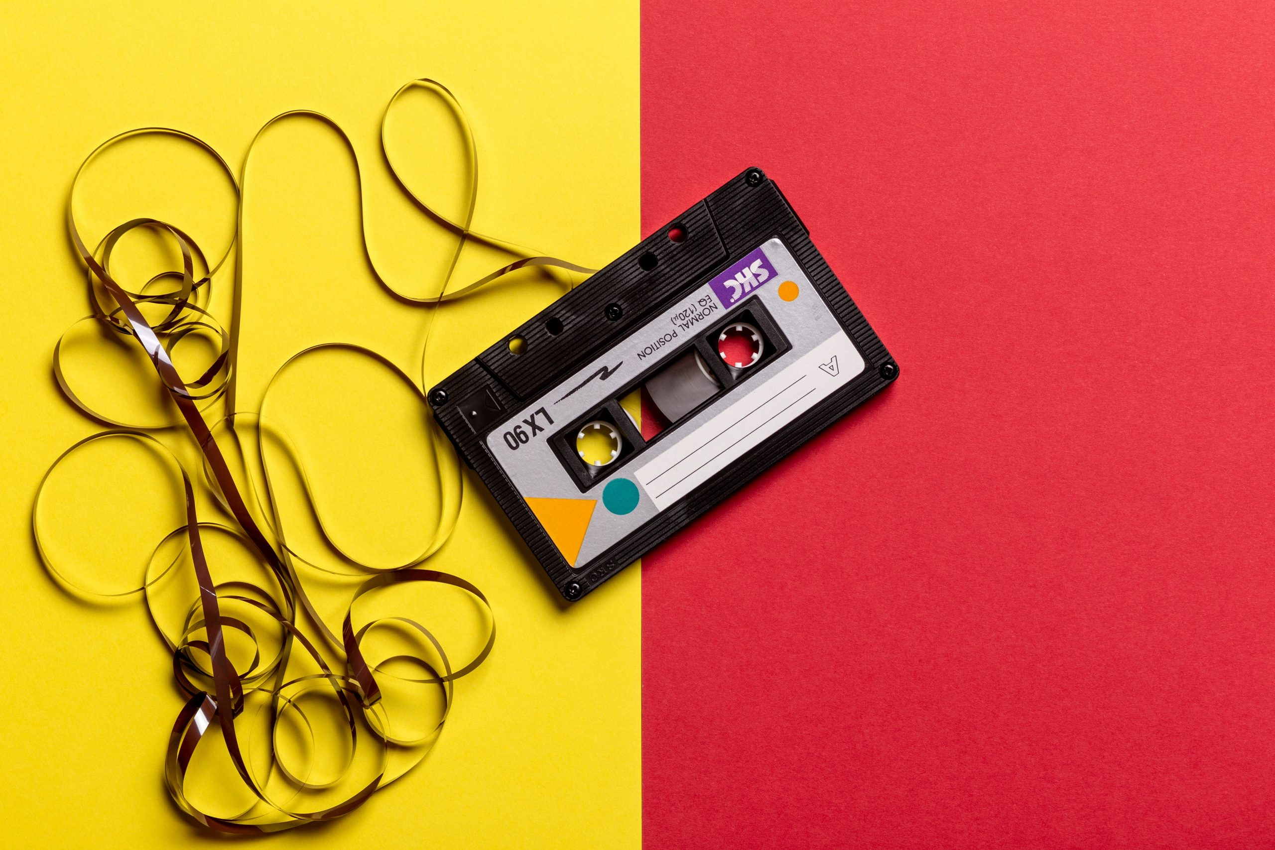 black-cassette-tape-on-top-of-red-and-yellow-surface